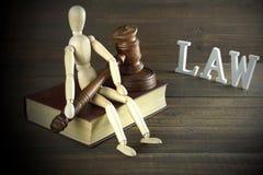 Estatuilla humana con los jueces o el mazo Sit On Book del subastador Fotografía de archivo