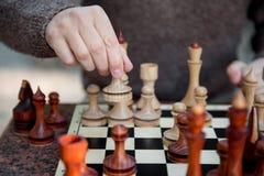 Estatuilla móvil de la mano masculina en el tablero de ajedrez imagen de archivo