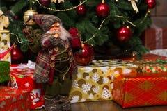 Estatuilla Santa Claus que sostiene un regalo que coloca el árbol de navidad cercano Fotografía de archivo