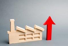 Estatuilla y rojo de la fábrica encima de la flecha El concepto de crecimiento en el nivel de producción y el desarrollo de la  foto de archivo