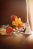 Estatuillas de la torta con el ramo en silla Fotos de archivo
