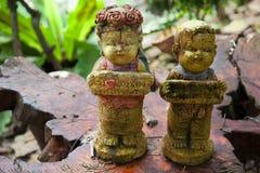 Estatuillas de piedra en un tablero de madera Foto de archivo libre de regalías