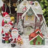 Estatuillas de Santa Claus delante de una casa nevosa Imágenes de archivo libres de regalías