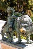 Estatuillas de un león de bronce y de un ángel fotografía de archivo