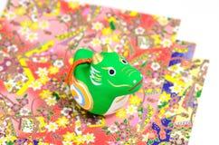 Estatuillas del dragón y papel alegre coloreado. Foto de archivo