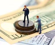 Estatuillas del líder del hombre de negocios y del consejero de las finanzas Billete de banco y moneda de los E.E.U.U. Fotos de archivo