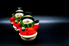 Estatuillas hechas a mano de los muñecos de nieve aisladas en fondo negro Decoración de la Navidad imagen de archivo