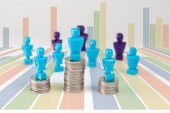 Estatuillas masculinas y femeninas que se colocan encima de pilas de la moneda con más allá del horizonte Fotos de archivo