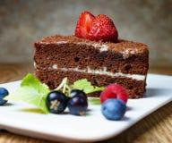 Este é um bolo delicioso do creme do chocolate, com morangos frescas, os corintos pretos e os mirtilos Em um fundo marrom delicad imagens de stock
