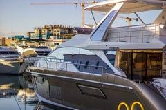 Este barco negro y blanco moderno amarrado en el puerto deportivo imagen de archivo