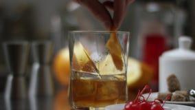 Este cocktail cl?ssico do bourbon U?sque de derramamento do empregado de bar no vidro com os cubos de gelo na tabela de madeira e video estoque