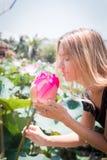 Este hermoso waterlily o flor de loto El control de la muchacha en sus manos una flor y una sonrisa foto de archivo libre de regalías