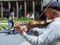 Este músico idoso está jogando sempre o violino para iluminar a plaza da independência imagem de stock royalty free
