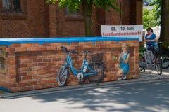 Este mural que representaba a una chica joven bonita que sonreía y que tapaba en una bici eléctrica azul fue visto en esta ciudad fotografía de archivo libre de regalías