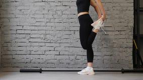 Este v?deo es mujer atl?tica alrededor de joven que estira los m?sculos de la pierna dentro en un gimnasio Estirando cierre de la almacen de metraje de vídeo