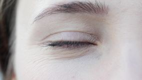 Este vídeo está sobre el primer tirado de ojo azul de la mujer hermosa atractiva con maquillaje y la concentración ligeros del dí almacen de video