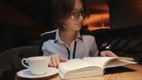 Este vídeo está sobre la abertura de la mujer joven y la lectura de un libro mientras que bebe el café en café acogedor metrajes