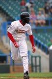 Estee Harris - runs to first base through the rain. CAMDEN, NJ - AUGUST 15: Camden Riversharks outfielder Estee Harris sprints to first base in the rain in a Royalty Free Stock Photos