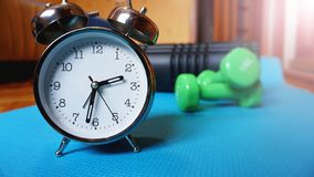 Esteira azul da ioga, dois pesos, despertador, rolo da auto-massagem - hora para o esporte imagem de stock