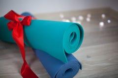 Esteira colorida dois da ioga com uma fita do presente fotos de stock