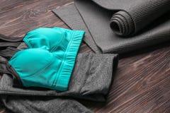 Esteira da ioga e sportswear fêmea no fundo de madeira imagem de stock