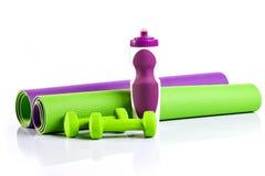 Esteira da ioga em um rolo exercícios da esteira Dois dumbbells verdes Fotografia de Stock Royalty Free