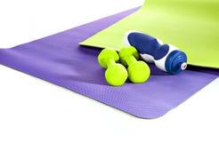 Esteira da ioga Exercícios azuis e verdes da esteira Dois dumbbells garrafa de w Foto de Stock Royalty Free