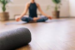 Esteira da ioga no fitness center com a mulher que medita na parte traseira imagens de stock