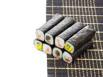 Esteira do bambu preto com o sushi isolado no fundo branco Foto de Stock Royalty Free