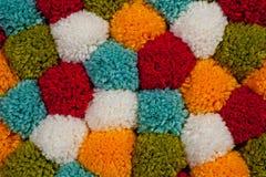 Esteira dos pompons feitos do fio feito a mão multi-colorido foto de stock