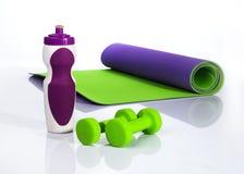 Esteira roxa da ioga, garrafa de água e dois pesos verdes Imagem de Stock