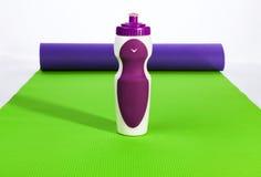 Esteira roxa dos esportes e da ioga da garrafa Imagens de Stock Royalty Free