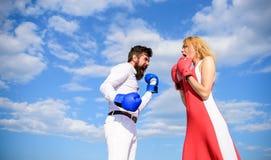 Esteja pronto defendem sua opinião do ponto O homem e a mulher lutam o fundo do céu azul de luvas de encaixotamento Defenda sua o fotos de stock