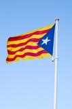 Estelada- the Catalan separatist flag. Waving over the blue sky Royalty Free Stock Photos