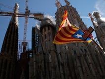 Independence flag waving next to sagrada familia cathedrala in barcelona. An estelada, catalonia pro independence flag, waves next to sagrada familia under Royalty Free Stock Photo