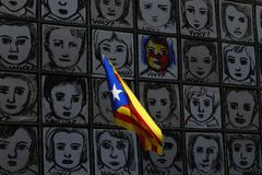 Catalonia flag waving next to Why wall art in Barcelonay banner. An estelada flag, Catalan separatist flag, waves next to the piece called Why by Carme Solé stock photography