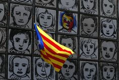 Catalonia flag waving next to Why wall art in Barcelonay banner. An estelada flag, Catalan separatist flag, waves next to the piece called Why by Carme Solé royalty free stock photography