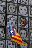 Catalonia flag waving next to Why wall art vertical. An estelada flag, Catalan separatist flag, waves next to the piece called Why by Carme Solé Vendrell in stock photo
