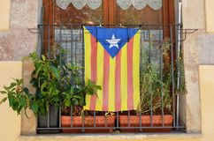 The Estelada in the window. The blue version of the pro-independence Catalan flag is on the metal lattice in the window. It is named the Blue Starred Flag Royalty Free Stock Image