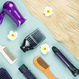 Estensioni degli strumenti e dei capelli di lavoro di parrucchiere su fondo di legno blu Vista superiore immagine stock