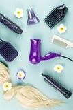 Estensioni degli strumenti e dei capelli di lavoro di parrucchiere su fondo di legno blu Vista superiore fotografie stock libere da diritti