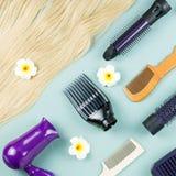 Estensioni degli strumenti e dei capelli di lavoro di parrucchiere su fondo di legno blu Vista superiore immagine stock libera da diritti