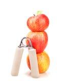 Estensore carpale e una pila di tre mele rosse Immagine Stock Libera da Diritti