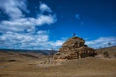 Estepe largo com grama amarela sob um céu azul com nuvens brancas e silhueta da menina sobre o monte, estepe de Tazheran foto de stock royalty free