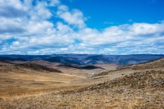 Estepe largo com grama amarela sob um céu azul com o estepe branco de Tazheran das nuvens, Sibéria Rússia imagens de stock royalty free