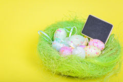 Ester eggs in nest with copy-space blackboard Stock Images