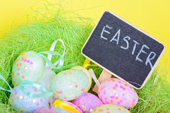 Ester eggs in nest with copy-space chalkboard Stock Photo
