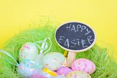 Ester eggs in nest with small blackboard Stock Photo