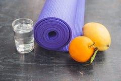 Estera, agua, naranja y mango de la yoga en un fondo de madera Equipo para la yoga Forma de vida, dieta y deporte sanos del conce Foto de archivo libre de regalías
