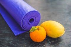 Estera, agua, naranja y mango de la yoga en un fondo de madera Equipo para la yoga Forma de vida, dieta y deporte sanos del conce Imágenes de archivo libres de regalías